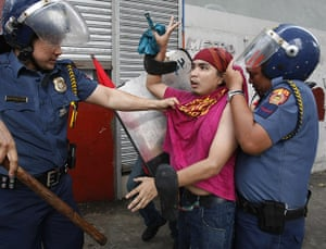 Occupy Mendiola: A protester flashes the peace sign as he is arrested by police, Manila