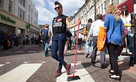 woman with broom clearing up in Clapham after the riots