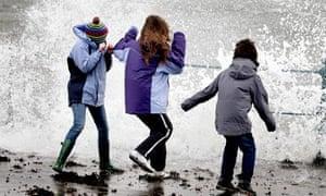 Children dodge waves in Scotland