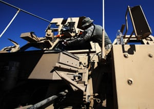 24 hours in pictures: US Army Specialist cleans the windshield of his vehicle , Iraq