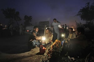 24 hours in pictures: Pakistani fruit vendors sit on a roadside waiting for customers