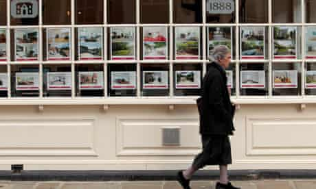 A woman walks past an estate agents in London