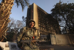 Egypt protests: An Egyptian soldier near the burnt National Democratic party building