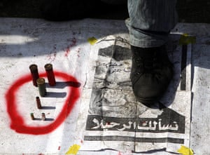Egypt crisis day 8: An Egyptian man steps on a banner placed on the ground
