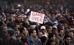 Egypt placards: An anti-government protester holds a sign in Tahrir square