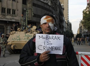 Egypt placards: A wounded demonstrator carries a poster in Cairo