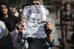 Egypt placards: An Egyptian man shows a sketch portraying President Hosni Mubarak