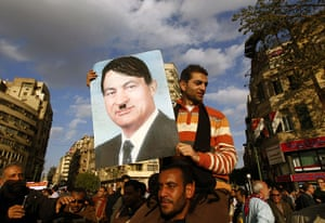 Egypt placards: A protester holds a placard depicting Hosni Mubarak as Adolf Hitler