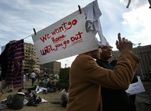 Egypt placards: Protesters stand under a placard in Tahrir Square
