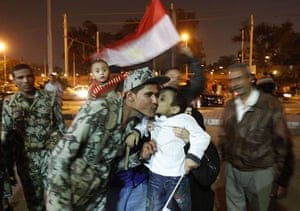 Mubarak resigns: An Egyptian boy kisses a soldier as anti-government protesters celebrate