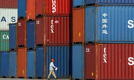 A Chinese worker walks past containers in Longwu Port in Shanghai