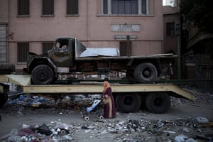 Egypt Day 19: An Egyptian woman walks with her baby in front of a burnt out vehicle