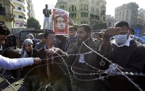 Egypt Day 19: An Egyptian removes razor-wire used at the barricades in Tahrir Square