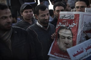 Egypt Day 19: Egyptians read a newspaper on the resignation of Hosni Mubarak