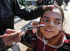 Egypt Day 19: An Egyptian man paints the Egyptian flag on a girls face at Tahrir Square