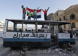 Egypt Day 19: Egyptian boys stand atop a destroyed bus in Tahrir Square