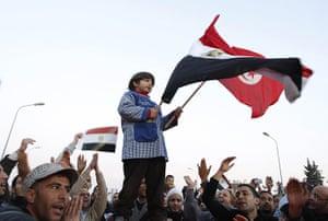 Egypt reaction: A boy waves an Egyptian and Tunisian flag