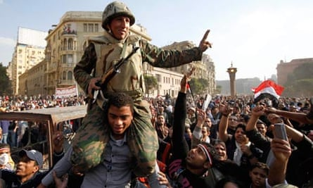 An Egyptian protester carries a soldier in Tahrir Square in Cairo