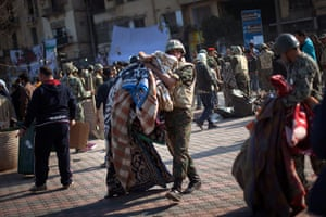 Egypt aftermath: An Egyptian Army soldier removes the blankets from protesters
