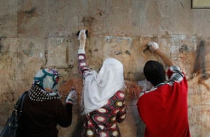 Egypt aftermath: Egyptian volunteers scrub paint and graffiti off of a wall