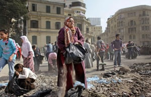 Egypt aftermath: Egyptian volunteers clean up debris e and rocks from the street