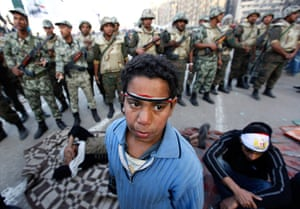 Egypt aftermath: An Egyptian protester boy stands in front of army soldiers