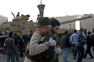 Egypt aftermath: An Egyptian man hugs an army commander at Cairo's Tahrir Square