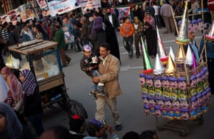 Egypt update: A man carries his son after buying him a mask in Tahrir Square