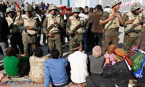 Protesters sit on the ground in front of soldiers in Tahrir Square, Cairo