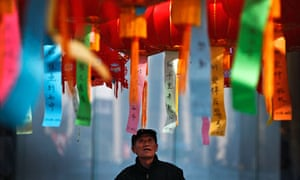 An elderly Chinese man looks at lanterns displayed outside a shopping mall in Beijing, China