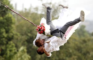 Valentine's Day: Prachinburi province, Thailand: A couple swing out on rappelling ropes