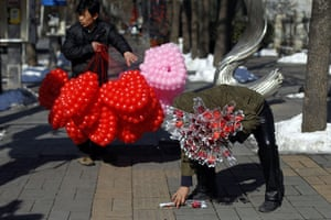 Valentine's Day: Beijing, China: A vendor selling roses and another selling balloons
