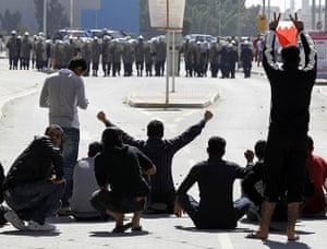 Arab unrest: Bahrain youths demonstrate in front of the police in Manama