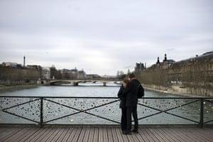 Valentine's Celebrations: A couple kiss on the Pont des Arts in Paris