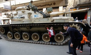 A man takes a picture of his daughter next to a tank in Tahrir Square, Cairo 14/2/11
