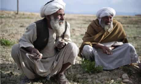 Afghan farmers work in a field as unseen