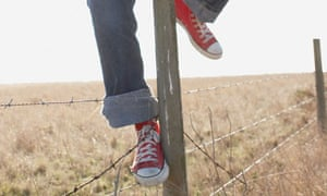 Sneakers climbing over barbed wire fence