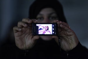 bahrain: A Bahraini anti-government demonstrator shows a pictures of a wounded man