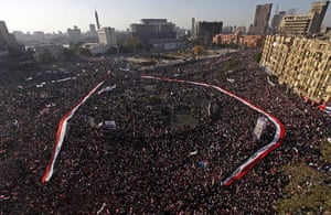 egypt: An Egyptian flag is held by the crowd around Tahrir Square in Cairo