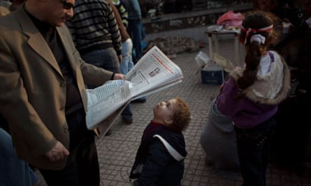 A young boy tries to read a newspaper in Cairo's Tahrir Square