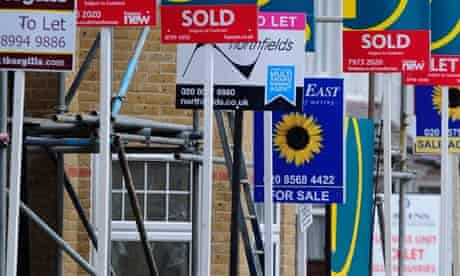 A woman passes house sales and letting signs