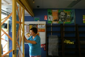 Cyclone Yasi preparations: Shop owner tapes up glass in preparation for Cyclone Yasi in Cairns