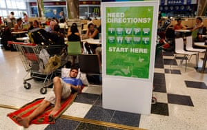 Cyclone Yasi preparations: A man sleeps in an emergency cyclone shelter at a shopping mall in Cairns