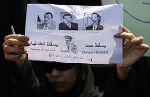 Arab protests: Manama, Bahrain: A Bahraini anti-government protester holds up pictures