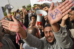 """Arab protests: Ramadi, Iraq: An Iraqi man shows writing on his palms saying """"Go out"""""""