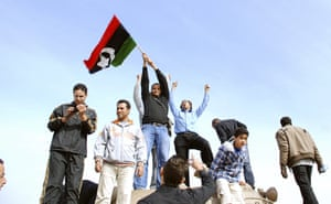 middle east unrest: Protesters stand on a tank in a security forces compound in Benghazi, Libya