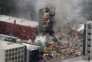 new zealand earthquake: Rescue workers work to extinguish a fire at a building in Christchurch