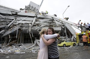 new zealand earthquake: Two console each other in front of a collapsed building