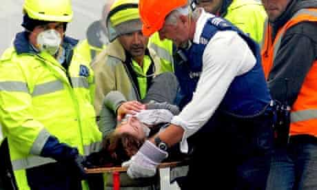 An injured person is carried by rescue workers after an earthquake hit Christchurch, New Zealand