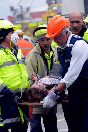 New Zealand earthquake: An injured woman is carried from the rubble of a collapsed block